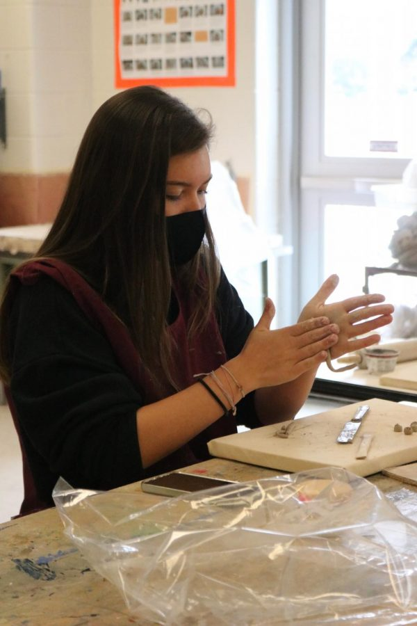 Senior Lydia Anderson works on making a clay sculpture in art class.