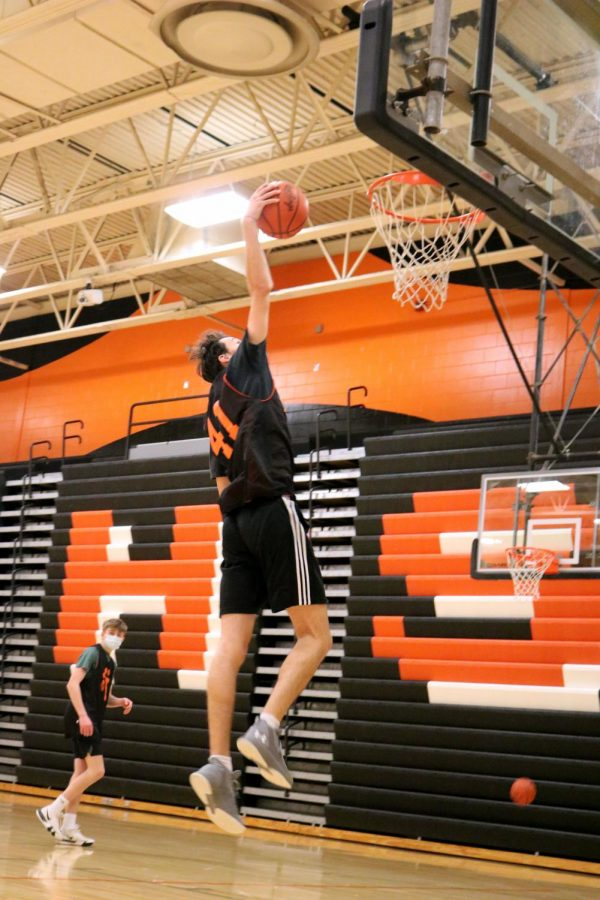 Junior Jasper Bakker goes up for a dunk during practice on Jan. 27. His teammates are cheering him on.