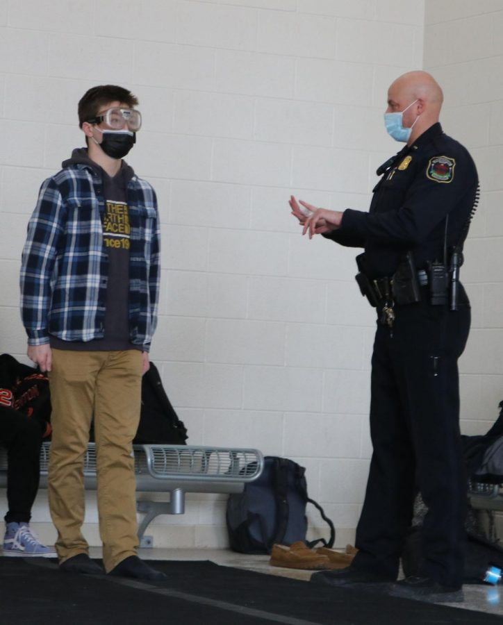 Attempting to walk in a straight line, senior Mason Church listens to instructions from Office Jeff Cross while participating in a 'drunk goggles' exercise. On Mon. 2/1 Officer Cross and Officer Tom Cole worked with Matt Sullivan's Forensic Science classes and involved students in a simulation activity in which their vision was impaired by a pair of goggles.