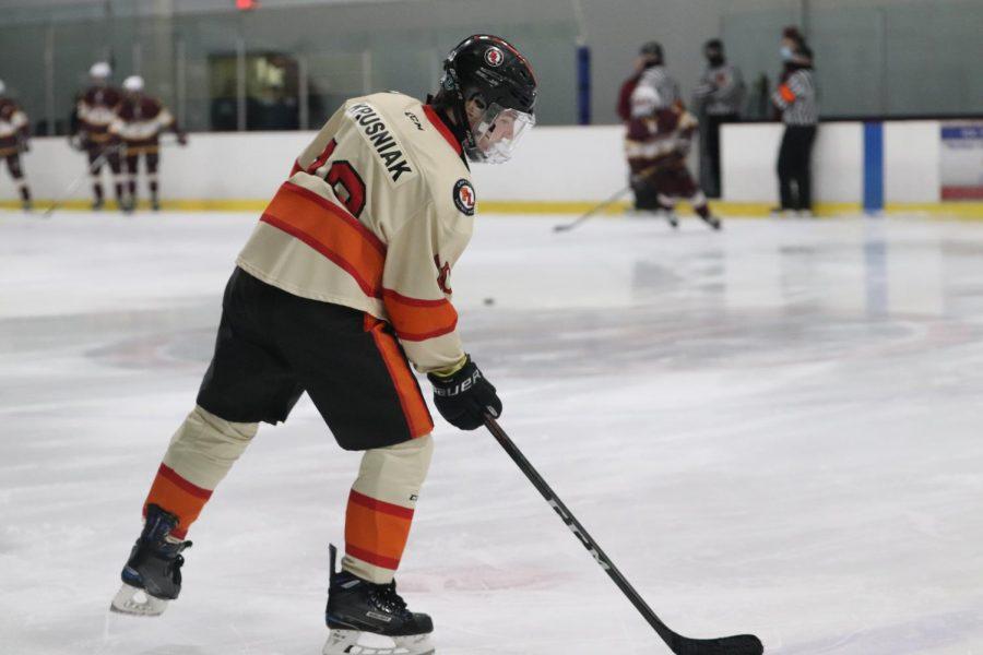 Senior Dominic Kruzniak prepares to pass the hockey puck to his teammate. On March 8, the varsity hockey team played Davison at home.