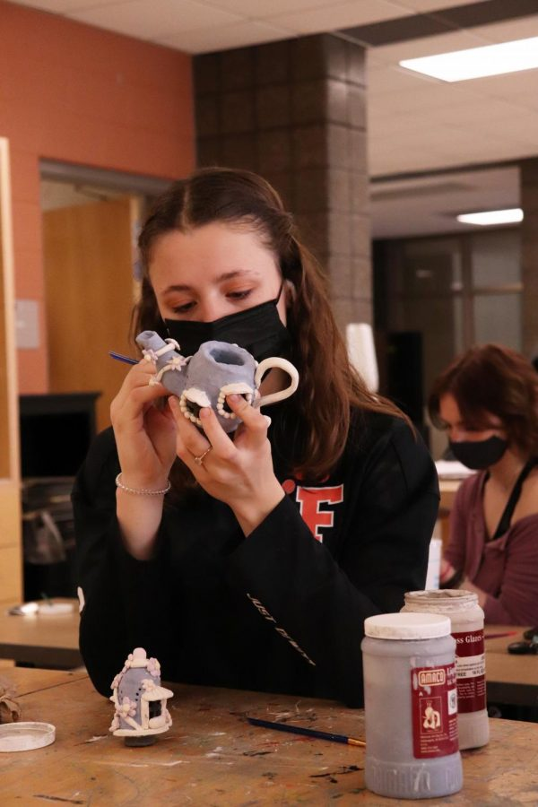 Working patiently, senior Hannah Ludwig paints her clay pot. On Mar. 16, Mrs. Jambeck's 2nd hour art class worked on sculptures.