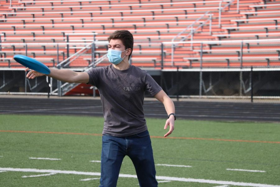 Freshman David Verna throws the frisbee across the field in his gym class.