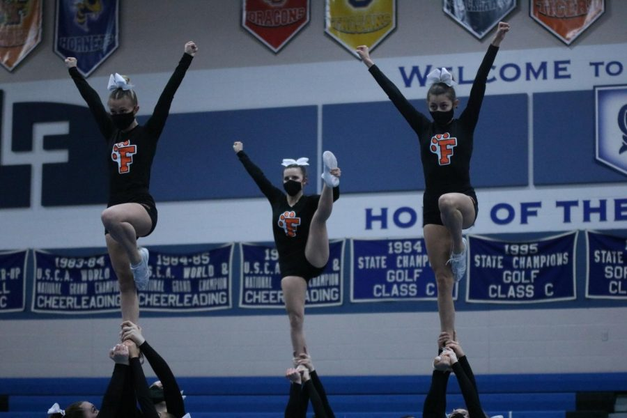 Junior Chlor Murray, senior Hailey Morcom, and junior Laura Singer doing stunts in the cheer meet on 2/26.