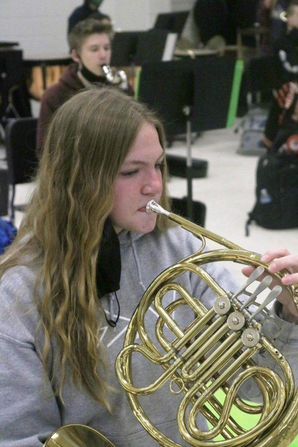 Freshman Julia Blanchard plays her french horn during band class,
