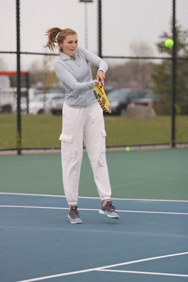 Junior Katelyn Burkett hits the tennis ball back over the net to the opposing team. On April 26, the girls varsity tennis team played Holly at home, winning 5-3.