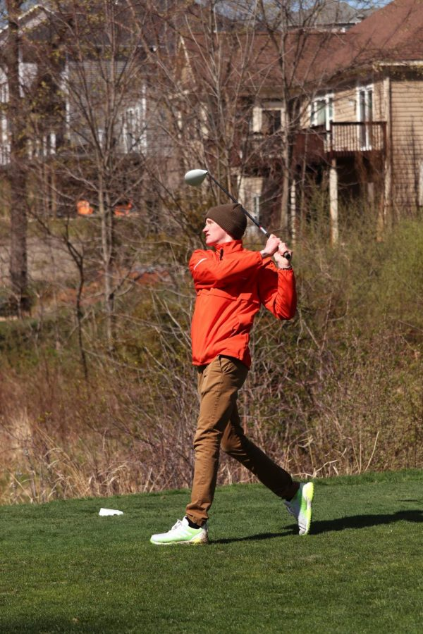 After hitting his drive, Senior Andrew Hutchins completes his follow through. On Apr. 21, the Tigers competing in the Genesee County Meet against many schools from the area.