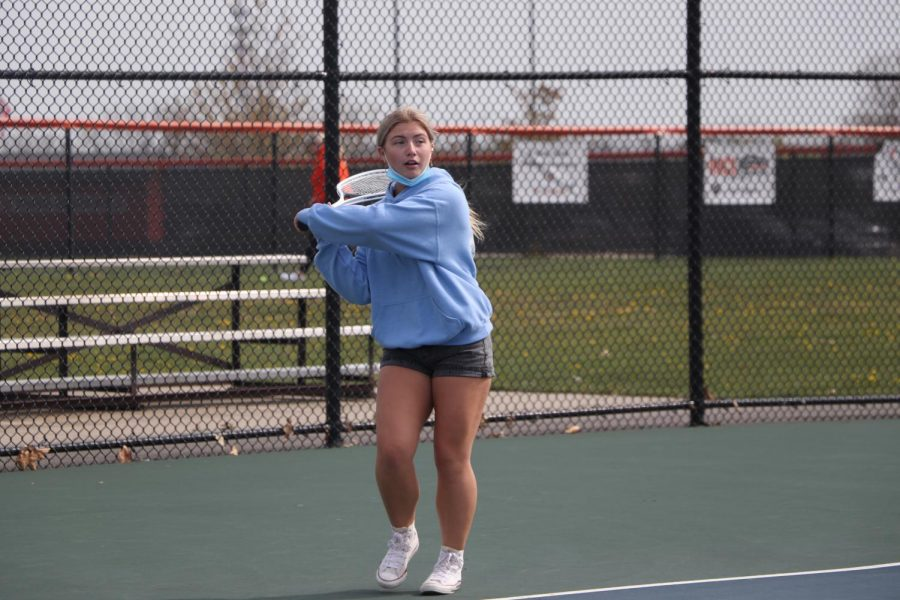 Freshman Evelyn Hall prepares to hit the tennis ball over the net while playing tennis outside during gym class.