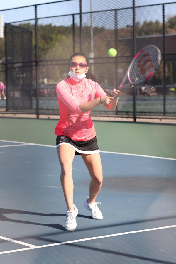 Junior Mai Nguyen swings at the tennis ball to send it back over the net toward her opponent. On April 30, the girls JV tennis team played Owosso at home.