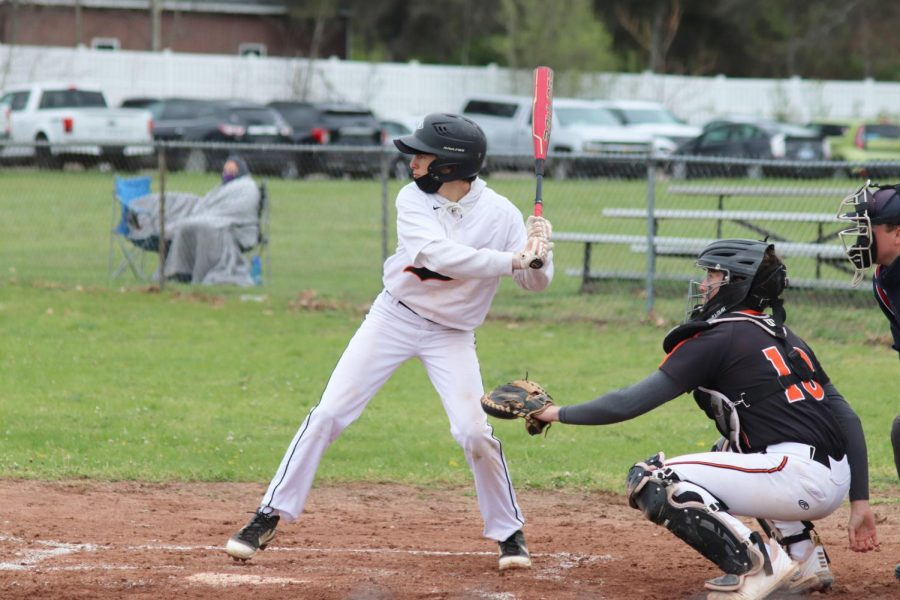 Freshman Nick Simeoni focuses on the pitcher before he swings his bat to hit the baseball into the outfield.