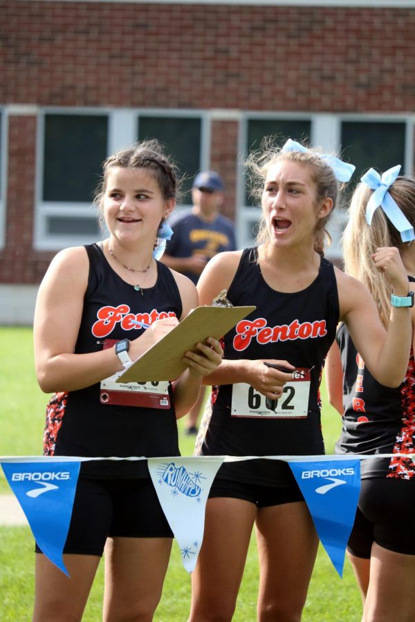 Junior+Abby+Logan+and+senior+Riann+Masi+cheer+on+their+teammates+through+the+finish+line.+On+Sep.+8%2C+all+of+Fentons+cross+country+teams+came+together+to+take+first+at+the+first++jamboree+of+the+year.