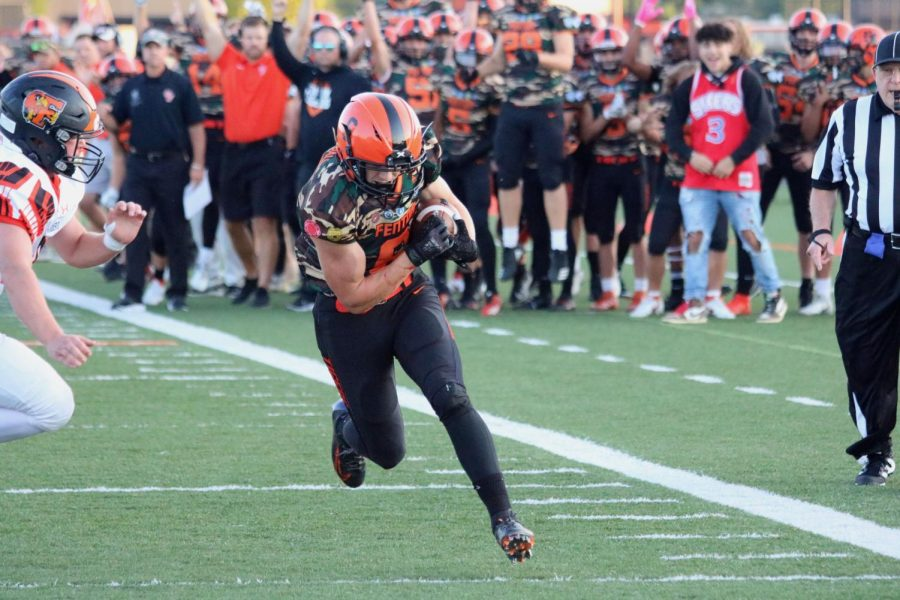 Sprinting+into+the+end+zone%2C+Sophomore+Jake+Nichols+scores+a+touchdown+for+the+varsity+Tigers.+On+Sept.+10%2C+the+Tigers+defeated+Flushing+39-20.