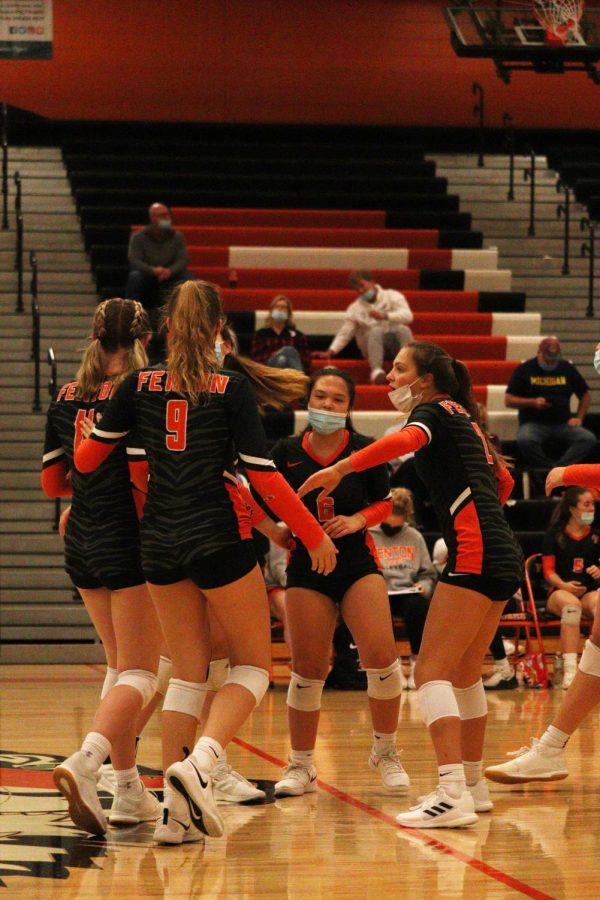 Cheering each other on, the Varsity volleyball team comes together to celebrate a good play. On Sept. 22, Fenton beat Kearsley 3-0.