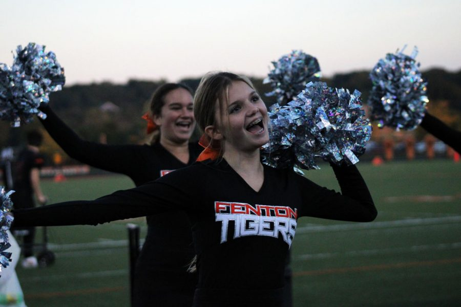 Freshman Olivia Kowalski cheers during half time with the rest of the JV cheer team. On Sept. 30 the JV cheer team cheers for the JV football team while playing against South Lyon.