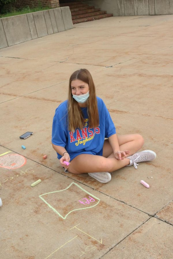 Junior Allie Lutz is talking to her group members while drawing the amendments with chalk on Oct. 7. In Shawn Lawrences history class they went outside and drew pictures to represent the amendments with chalk.